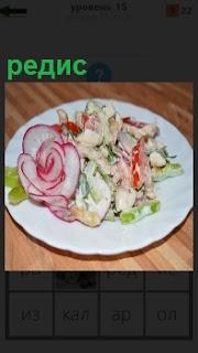 На тарелке на столе приготовлен салат из редиса вместе с остальной зеленью и овошами