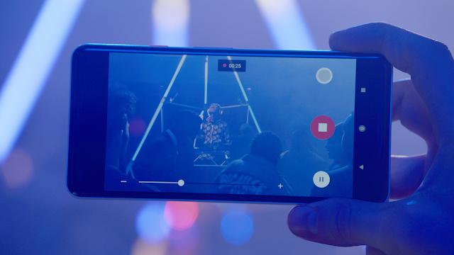 Ein Handy filmt einen Musiker auf der Bühne