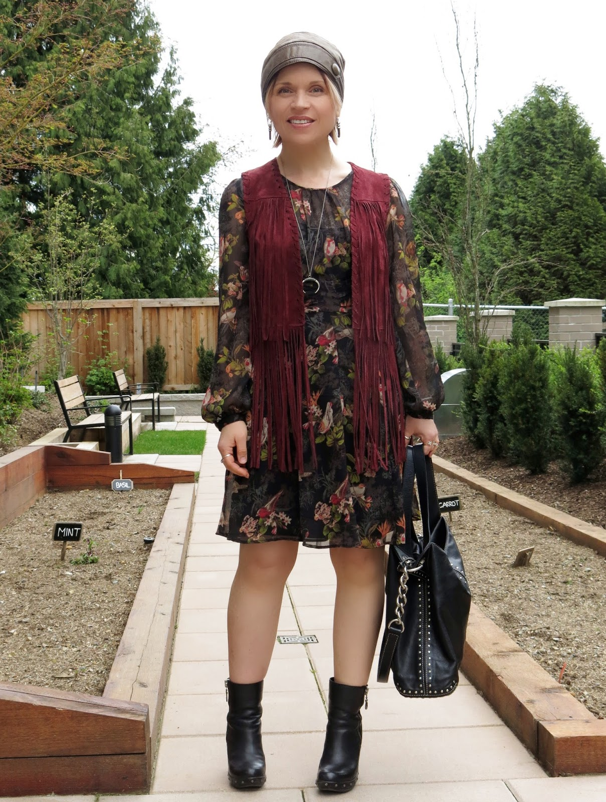 styling a floral dress with a fringy suede vest, platform booties, and leather beanie