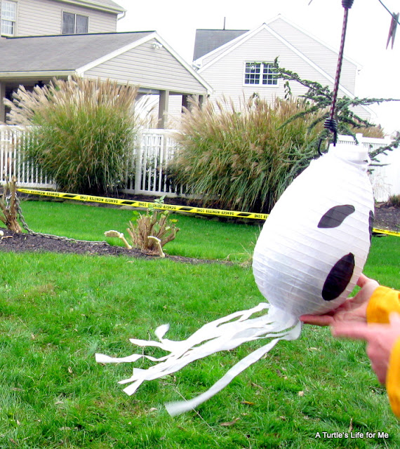 A paper lantern decorated like a ghost turned into a pinata