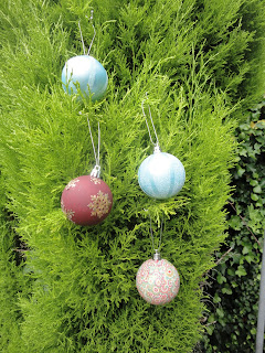 Four decorated baubles in a fir tree