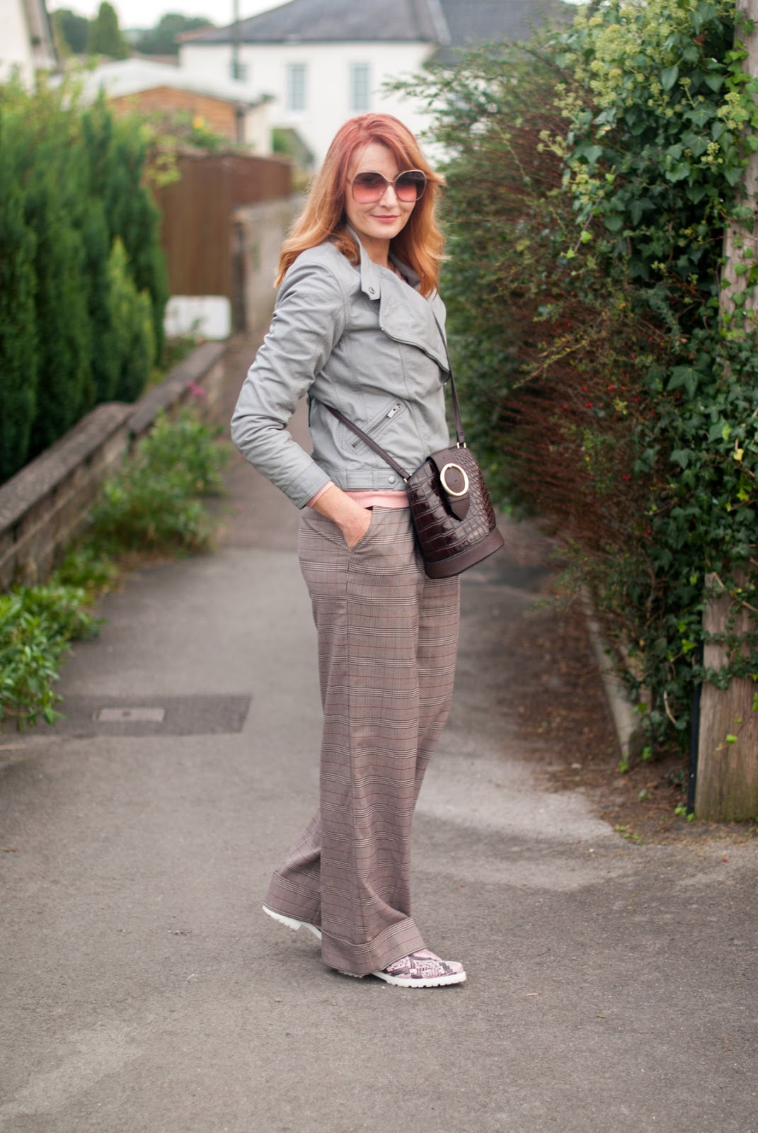 Smart but comfy autumnal dressing: Grey leather biker jacket \ millennial pink sweater \ brown check wide leg pants \ pink snakeskin shoes | Not Dressed As Lamb, over 40 style