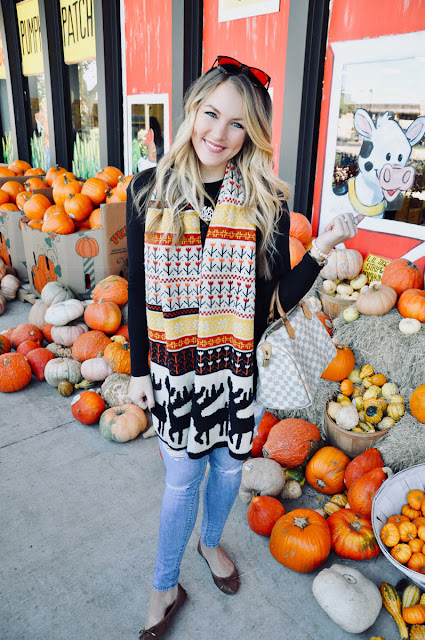 Girl in pile of pumpkins