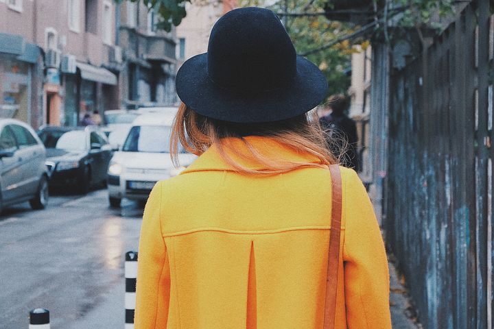 Woman in yellow coat and black hat