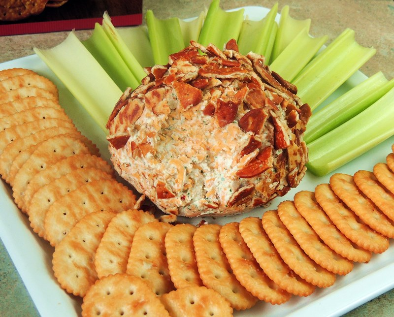 Buffalo Ranch Cheese Ball on a white platter with chips and veggies.