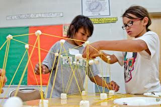 Two children build bridge with spaghetti and marshmallows