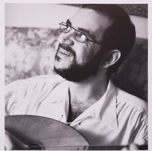 Foto de Renato Russo segurando um violão e olhando para o lado.  Foto esta em preto e branco.