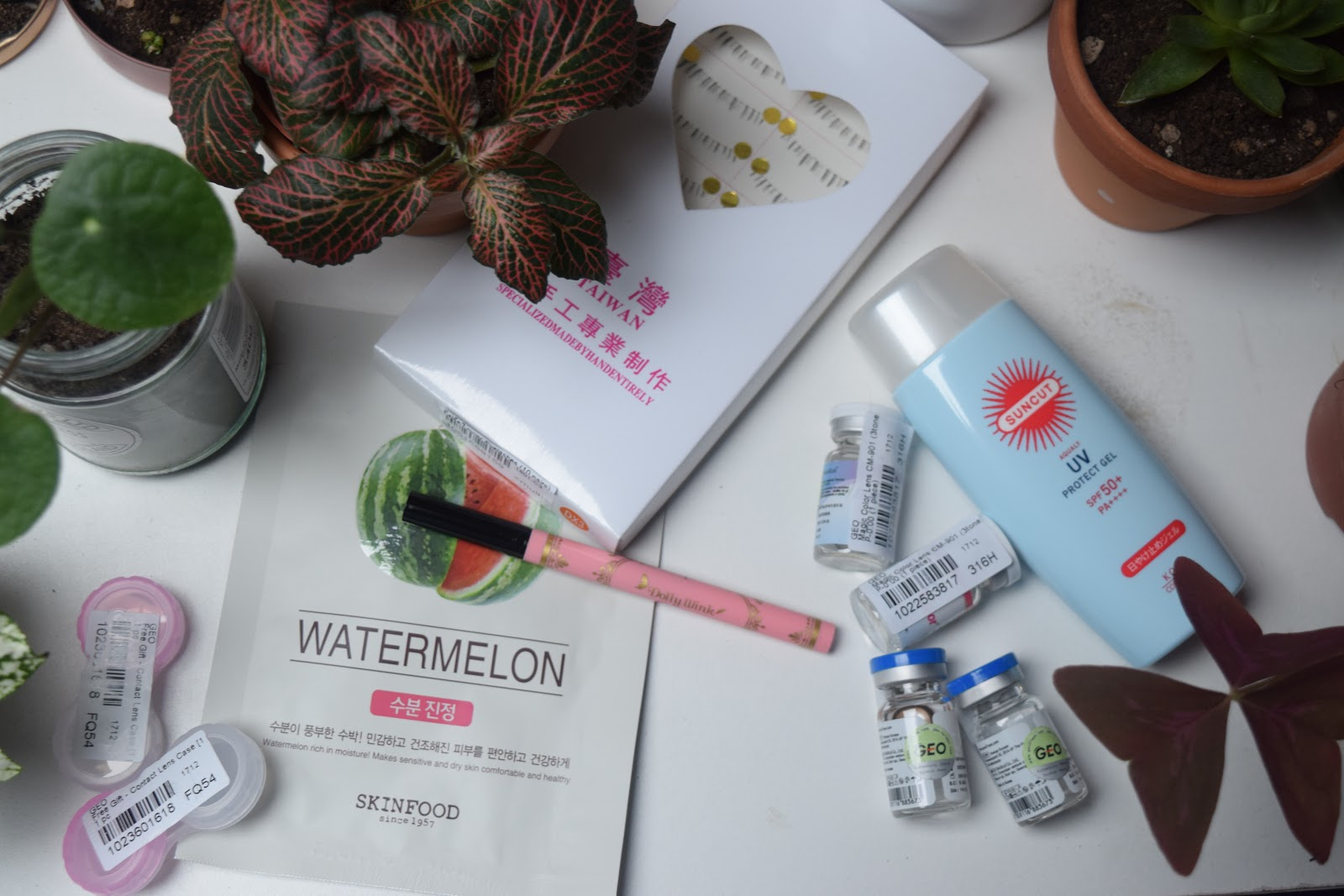 Asian cosmetics flatlay including Kosé sunscreen, Dolly Wink liquid eyeliner, Skinfood, GEO