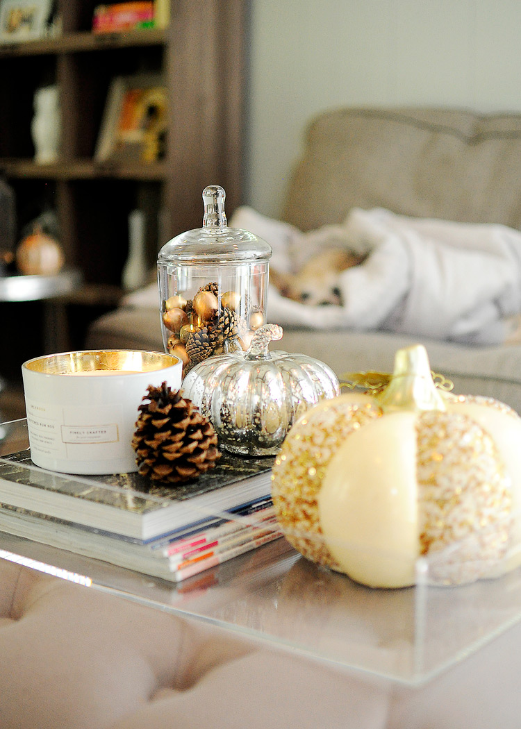 Mercury glass pumpkin, gold sequin gourd, and pinecone with candle on a lucite tray on an ottoman for fall living room decor. | #falldecor #livingroomdecor #livingroomideas #monicawantsit