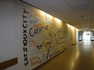 "this mural in the Sioux City Skywalk system was painted as part of an event called Innovation Market and features inspiring words like ""spark"" and ""goals"" in black, orange, spring green, and sky blue on a white wall in the Sioux City Skywalk system"
