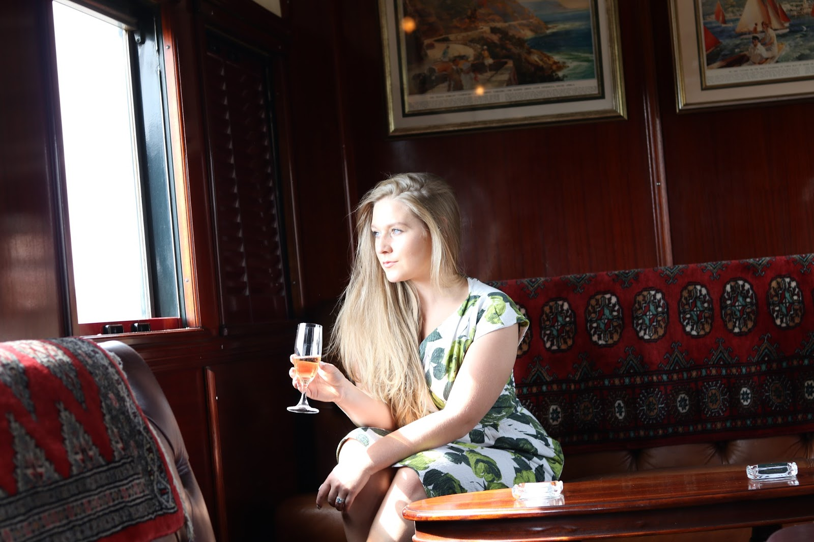 Blonde girl, Katie Heath sipping champagne on Rovos Rail