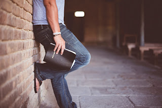 Transformed by truth - hipster holding bible leaning on brick wall