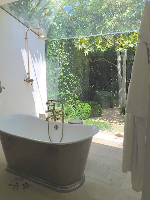 Bathroom tub area with gold shower and window to the backyard