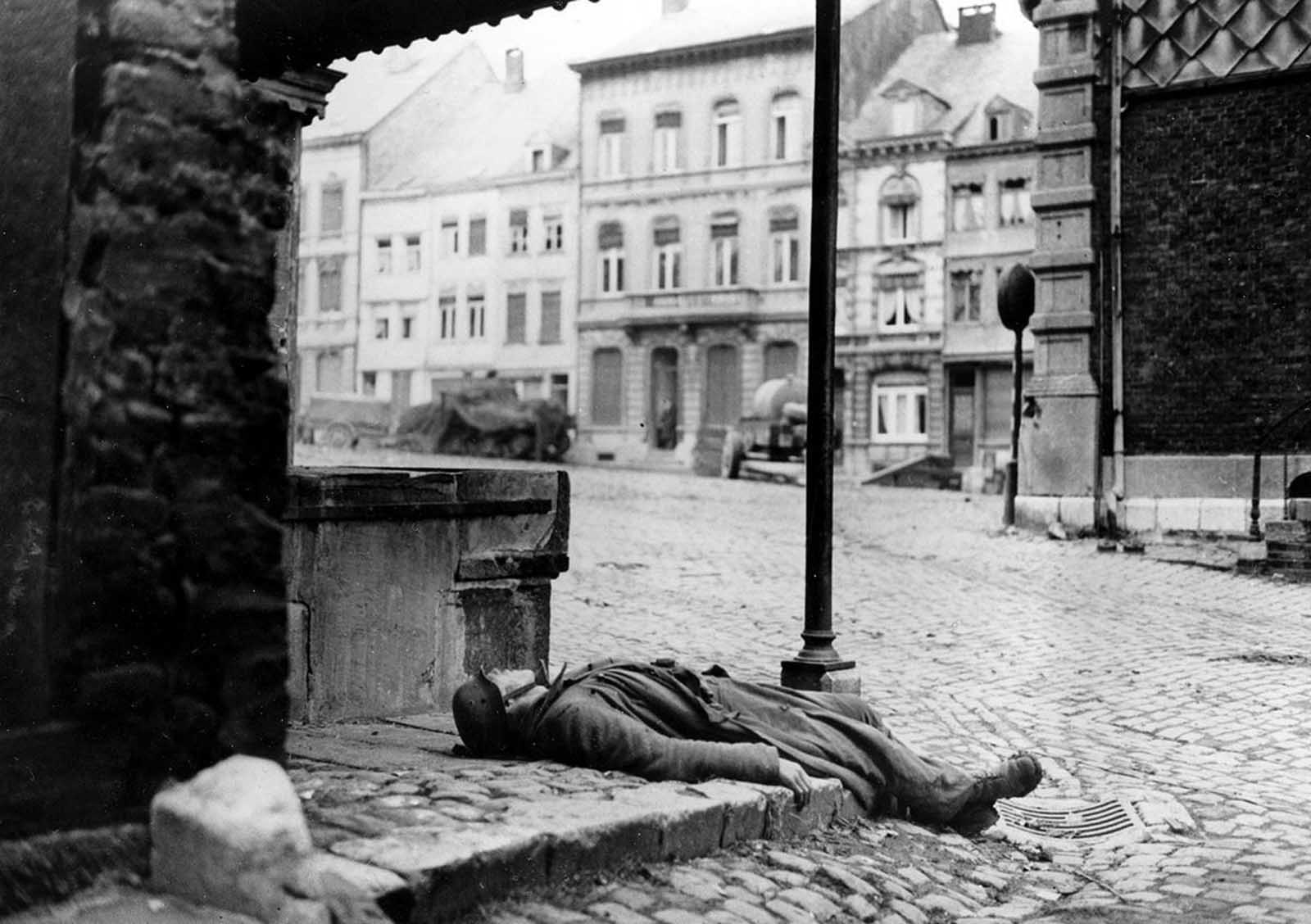 A dead German soldier, killed during the German counter offensive in the Belgium-Luxembourg salient, is left behind on a street corner in Stavelot, Belgium, on January 2, 1945, as fighting moves on during the Battle of the Bulge.