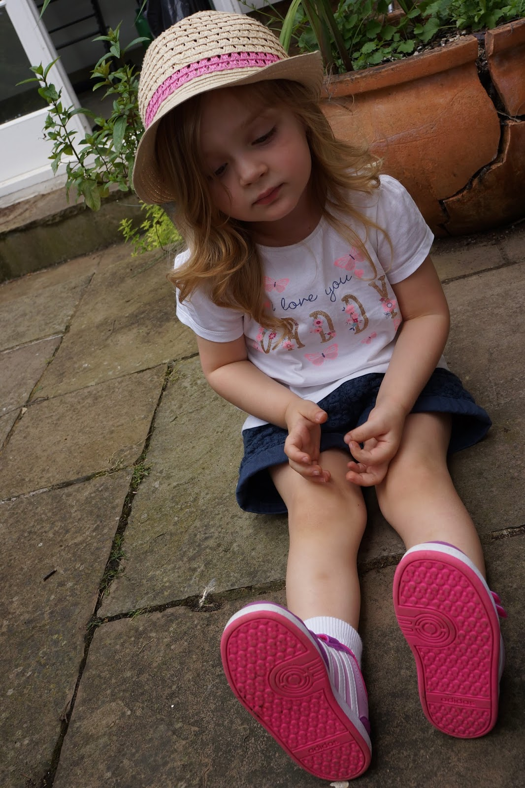 toddler girl sitting in the garden wearing i love you daddy t shirt