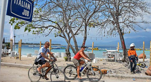 Two foreign tourists riding bicycles in the Gili Trawangan tourist area, Gili Indah Village, Pemenang District, Tanjung, North Lombok, NTB, Wednesday (08/08/2018). After the earthquake that struck the North Lombok area, some foreign tourists chose to remain in the tourist area of Gili Trawangan. (ANTARA PHOTO / AHMAD SUBAIDI)