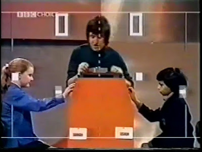 "Photo of Ed ""Stewpot"" Stewart moderating a game of televised football-pong super-imposed over two children facing one another with hands on their game paddle controls."