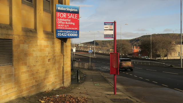 'For sale' sign and bus-stop.