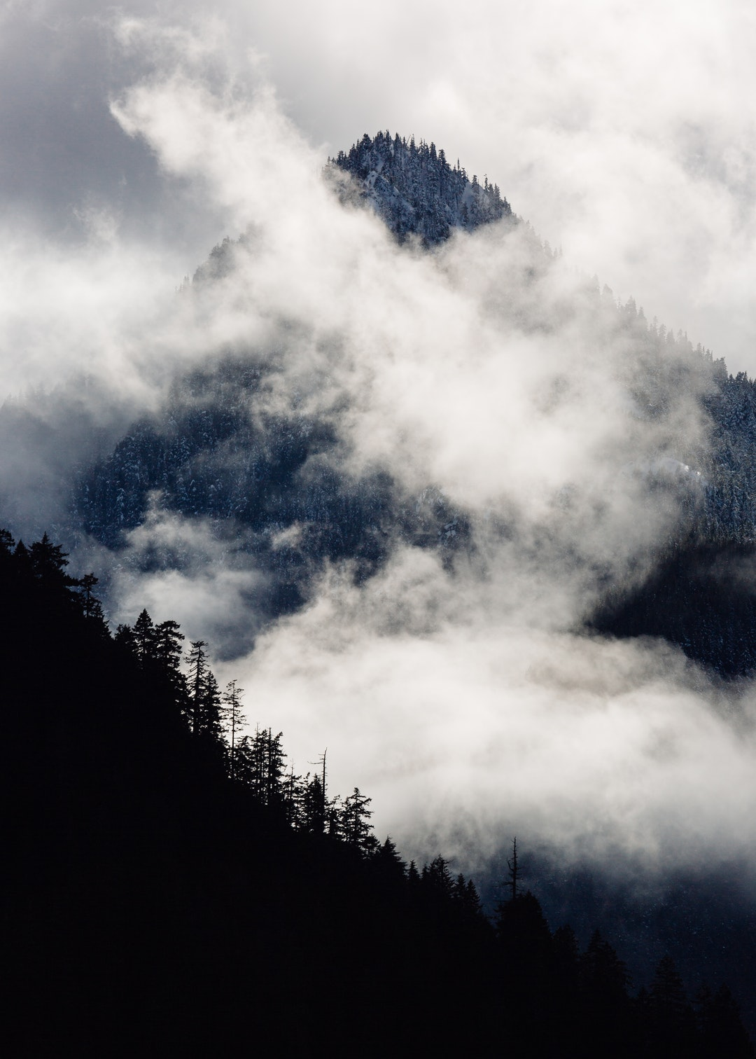 جبل بركاني ثائر ازرق مع ضباب كثيف و غابة - خلفيات ايفون X