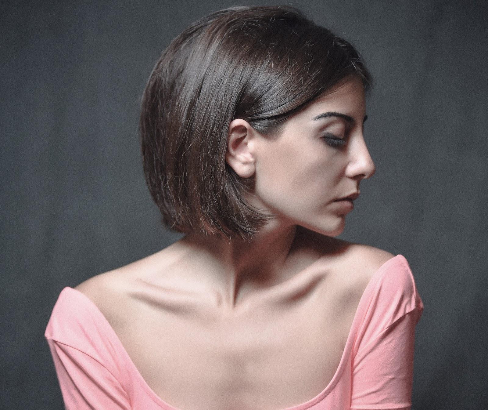 胸元を開けた桃色の服の左向きの横顔の髪の短い女性
