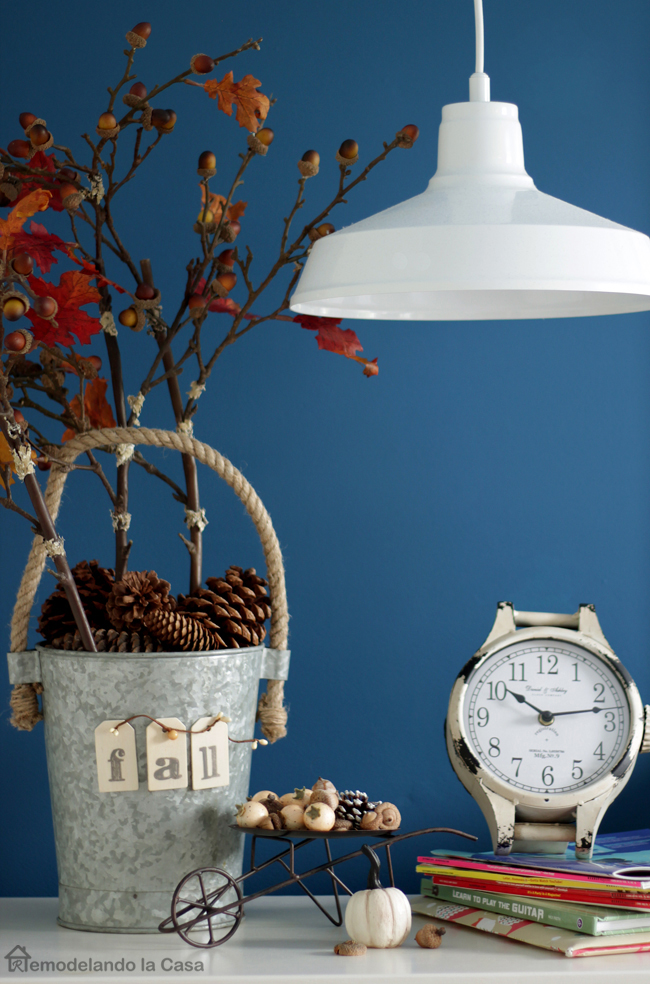 a pail of pine cones with a little wheelbarrow, pumpkins, old clock and books