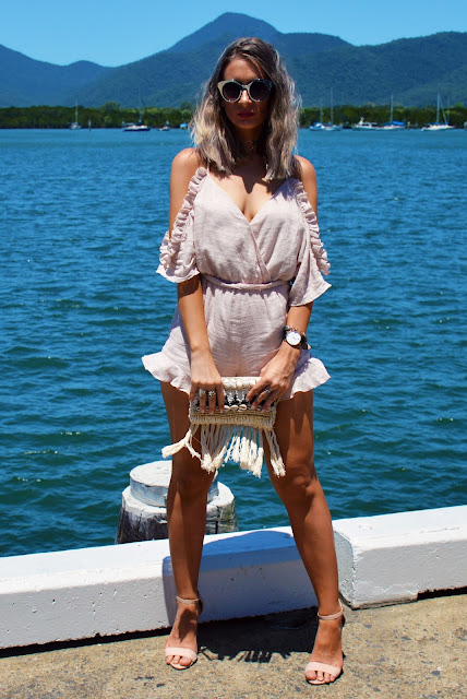 cute ruffled summer playsuit styled with nude heels sunglasses and a fringe clutch bag