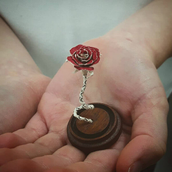 miniature red rose paper sculpture made from a book page and held in a hand palm.