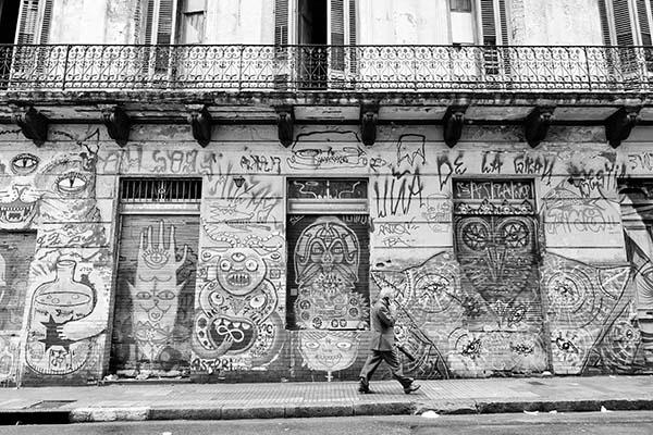 Frente de una casa antigua con pintadas en paredes y aberturas