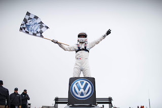 Race-car driver Romain Dumas atop the Volkswagen I.D. R Pikes Peak electric race car.