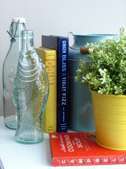These glass vases with a yellow flower pot and plant look cute.