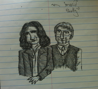 The second of the three drawings/notes in my notepad. The image is of two people. On the left, a man with a long beard and no mustache, curly hair and beard, round glasses, wearing a short-sleeved shirt, and who has hairy arms. He appears to be smiling. On the right, a woman with long, straight hair, and evenly cut bangs, dressed in a tunic-style top, who also appears to be smiling. Beside and below that are illegible notes.