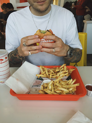 A picture of a man eating an In N Out burger at Fishermans Wharf, San Francisco