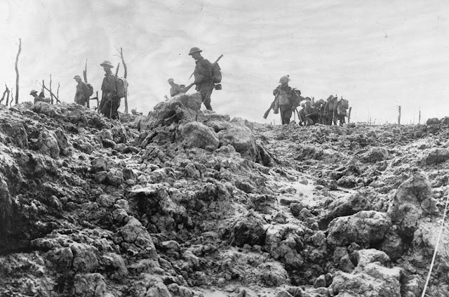 Original caption: Advancing over No Man's Land. Troops moving forward over ground that has been thoroughly churned up by shells from big guns, July, 1918.