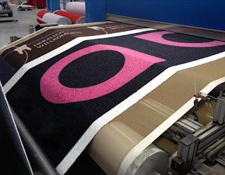 Design und Logo werden im Vorfeld gemeinsam mit dem Kunden festgelegt. Ein Spezialdrucker überträgt die Farben auf den Flor aus High-Twist-Nylon, fixiert und versiegelt diese.