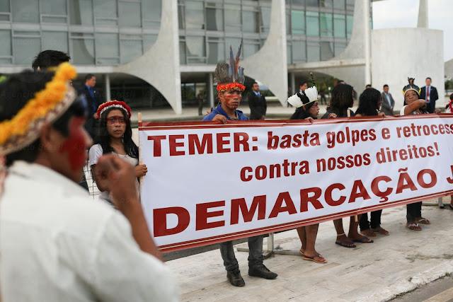 Foto de índios na frente do palácio do planalto segurando uma faixa que diz: Temer, basta golpe e retrocesso contra nossos direitos. Demarcação Já!