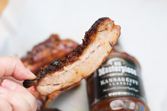 A single rib being help over a bottle of sauce.