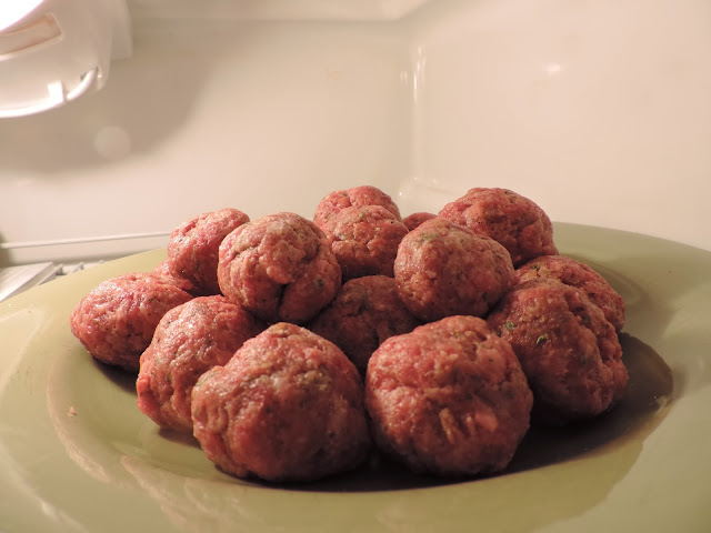 The formed meatballs on a place in the refridgerator.
