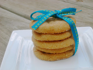 peanut butter cookies stacked on a white plate with blue ribbon