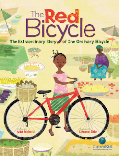 Book cover: 'The Red Bicycle' by Jude Isabella. A young girl stands holding a red bicycle amid a market scene of baskets on the ground that hold a variety of goods. In the background, a woman sits in the shade of an umbrella.