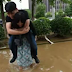Chinese woman  carrying her boyfriend on her back while crossing a flooded street so 'he won't ruin his expensive leather shoes'