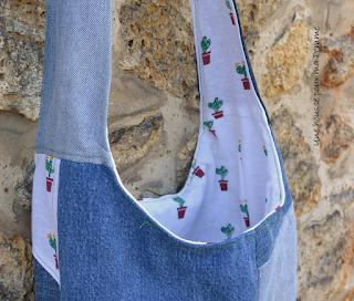 """Sac bandoulière fait de pans de pantalons en jeans recyclés (chinés par mes soins), de différents tons, montés façon patchwork, coutures surpiquées de fil vert, bandoulière en jeans, entièrement doublé en tissu coton au motif cactus. Les jeans portés recyclés parfois délavés par le temps apportent cette """"petite chose en plus"""" à cette pièce unique. Dimensions : 35 x 33 x 8 cm, hauteur avec la bandoulière : 83 cm."""