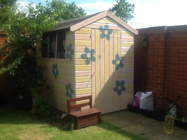 Pink and Yellow Striped Shed with Blue Flowers