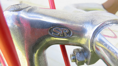Bicycle Handlebar stem with red reflection of brake wire