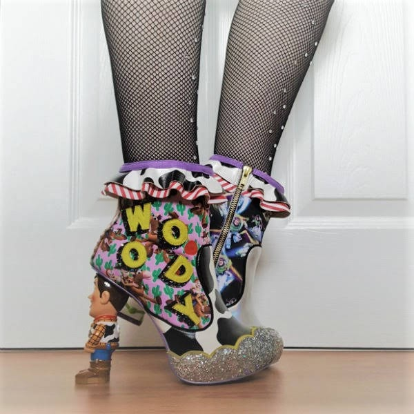 side angle of legs in black fishnets with cow print ankle boots and Woody Toy Story heel