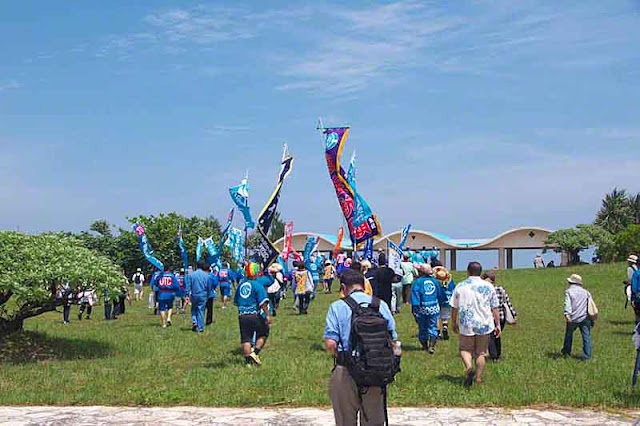 procession, shore, sea, grass, people, banners, Okinawa