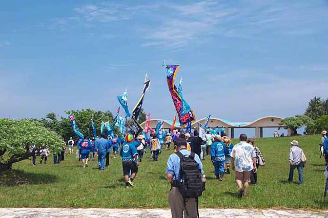 procession, shore, sea, grass, people, banners, Okinawa