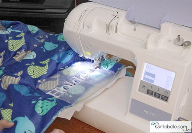 Learn how to use an embroidery machine to add a name to a baby blanket. Video tutorial by Karlie Belle.