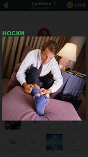 Мужчина сидя на кровати одевает носки, но они с дыркой на пальцах