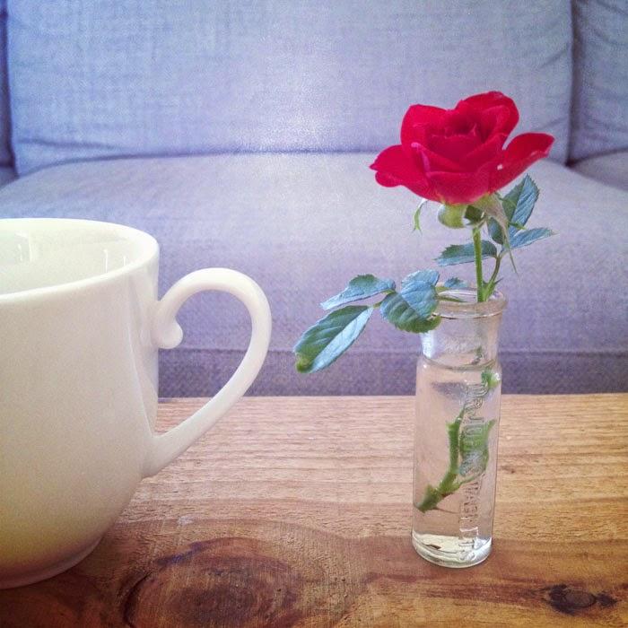 アンティークのガラスボトルにミニバラを活けてカップと並べた