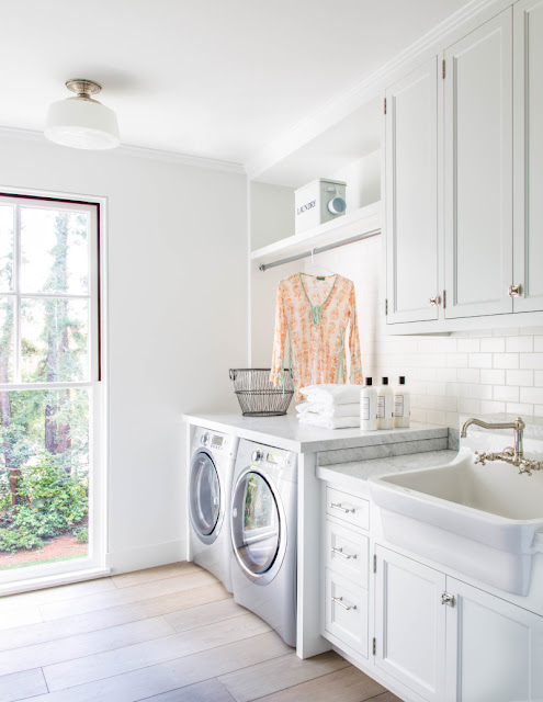 Bright white modern farmhouse laundry room by Giannetti Home with country farm sink